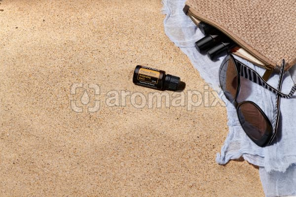 doTERRA Citrus Bliss with sunglasses, scarf and roller bottles in a clutch on the beach.
