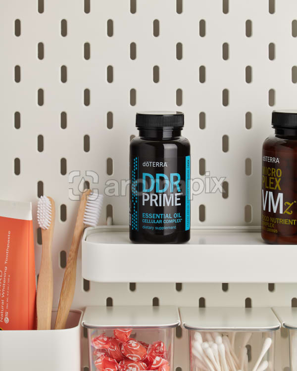 doTERRA DDR Prime Softgels on a bathroom shelf with additional doTERRA products and bathroom accessories.