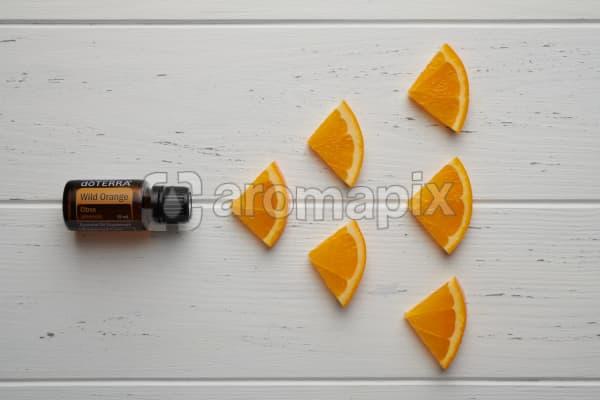 doTERRA Wild Orange oil and orange pieces on white rustic wooden background.