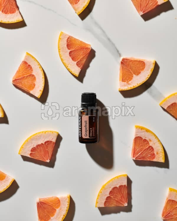 doTERRA Grapefruit essential oil and slices of grapefruit scattered on a white marble background.