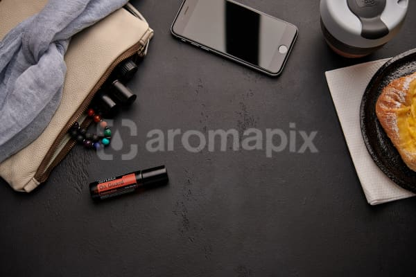 doTERRA On Guard Touch with a leather clutch, roller bottles, cell phone, coffee and food on a black background.