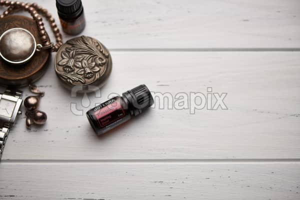 doTERRA Passion blend, jewellery and trinkets on white rustic wooden background.