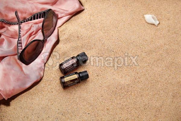 doTERRA Wintergreen and Tangerine with sunglasses and a pink silk scarf on the beach.