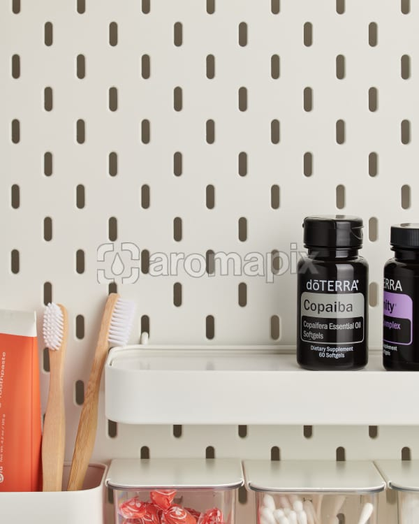 doTERRA Copaiba Softgels on a bathroom shelf with additional doTERRA products and bathroom accessories.