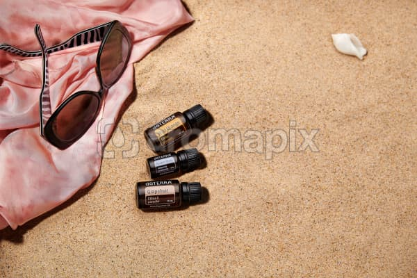 doTERRA Wild Orange, Juniper Berry and Grapefruit with sunglasses and a pink silk scarf on the beach.