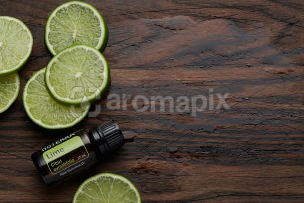 doTERRA Lime oil and slices on rustic wooden chopping board.