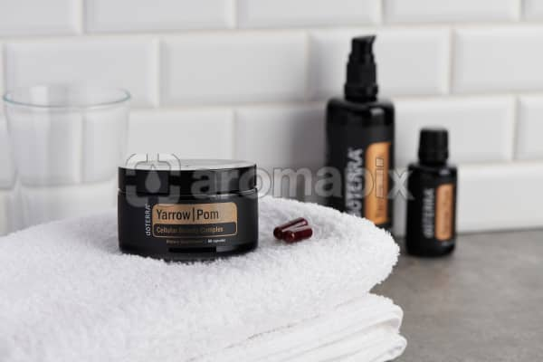 doTERRA Yarrow Pom, Body Renewal Serum and Cellular Beauty Capsules on a white towel on a gray stone bathroom bench top.