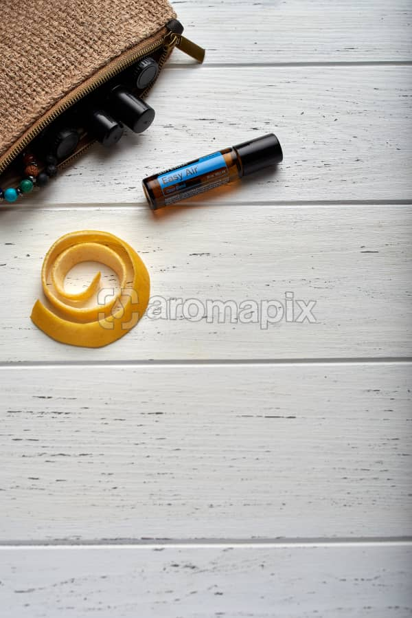 doTERRA Easy Air Touch, lemon peel and clutch with oils on white wooden background.