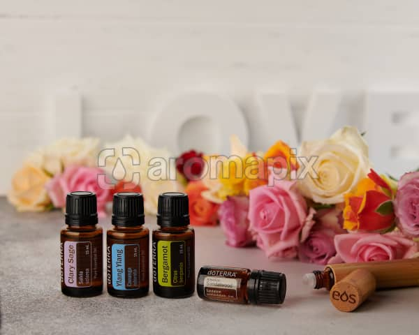 doTERRA Clary Sage, Ylang Ylang, Bergamot and Hawaiian Sandalwood with a bamboo roller bottle and roses on a concrete bench top.