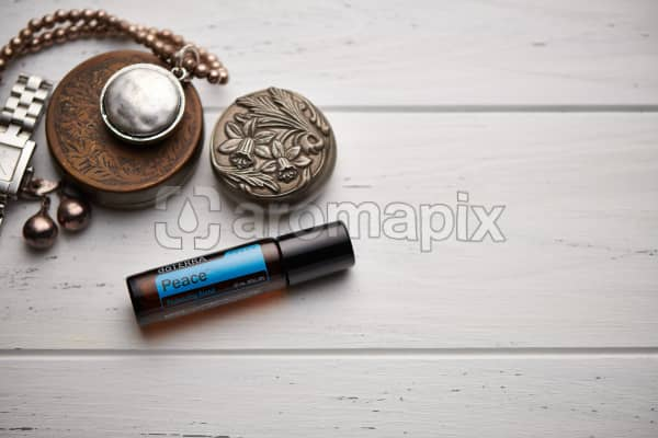 doTERRA Peace Touch blend, jewellery and trinkets on white rustic wooden background.
