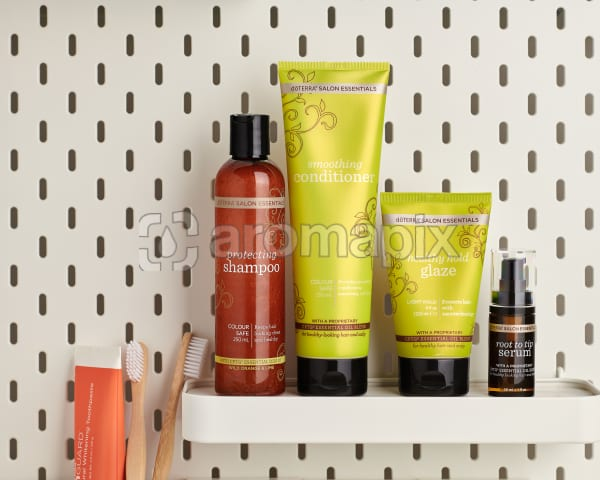 doTERRA Salon Essentials including Protecting Shampoo, Smoothing Conditioner, Healthy Hold Glaze and Root to Tip Serum on a bathroom shelf with bathroom accessories.