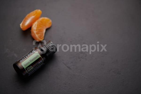 doTERRA Green Mandarin oil and mandarin pieces on black concrete background.