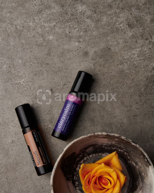 doTERRA Neroli Touch and ClaryCalm with an orange rose in a bowl on a gray stone background.