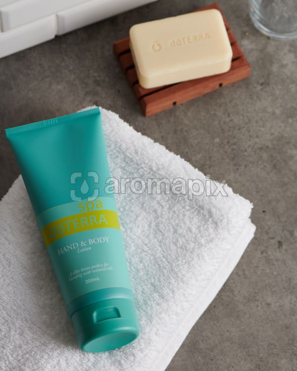 doTERRA Spa Hand and Body Lotion on a white fluffy towel with a Moisturizing Bath Bar on a gray stone bathroom bench top.