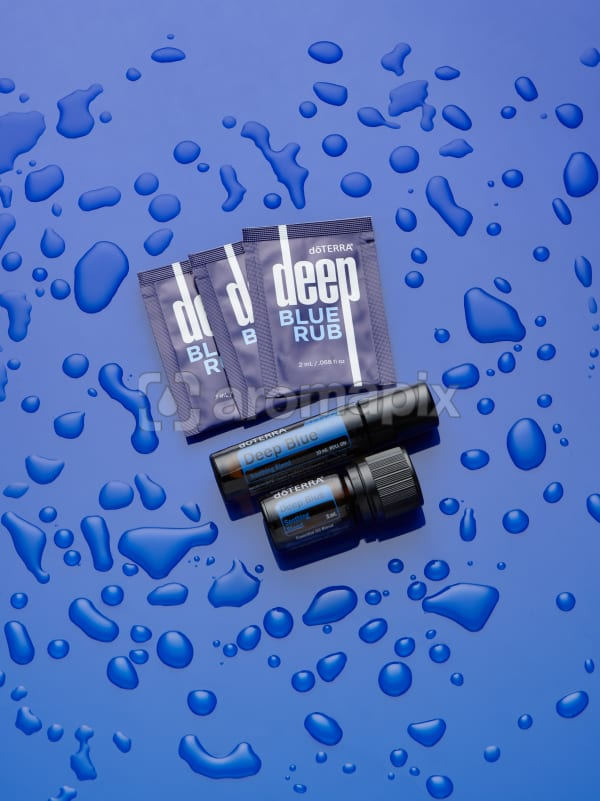doTERRA Deep Blue Rub, Athletic Blend Roll On and Athletic Blend 5ml on blue perspex with water drops.