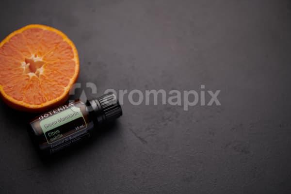 doTERRA Green Mandarin oil and mandarin slice on black concrete background.