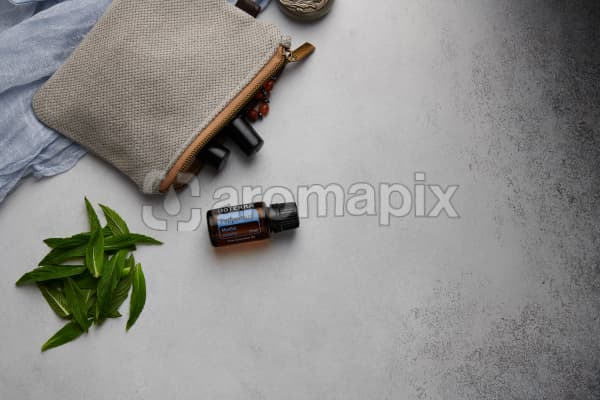 doTERRA Peppermint with clutch, accessories and mint leaves on a white concrete background.