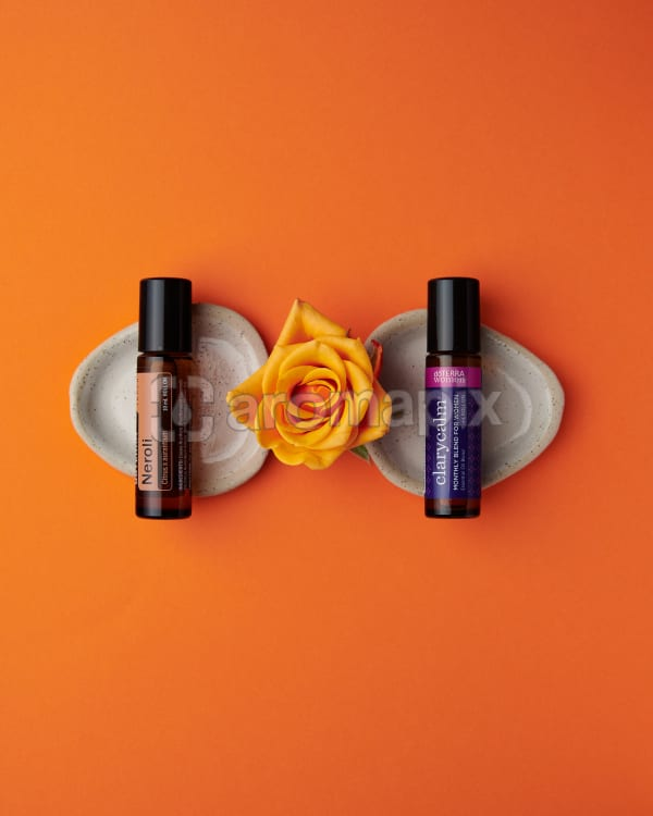 doTERRA Neroli Touch and ClaryCalm with a rose on a orange background.