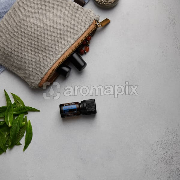 doTERRA Ice Blue with clutch, accessories and mint leaves on a white concrete background.