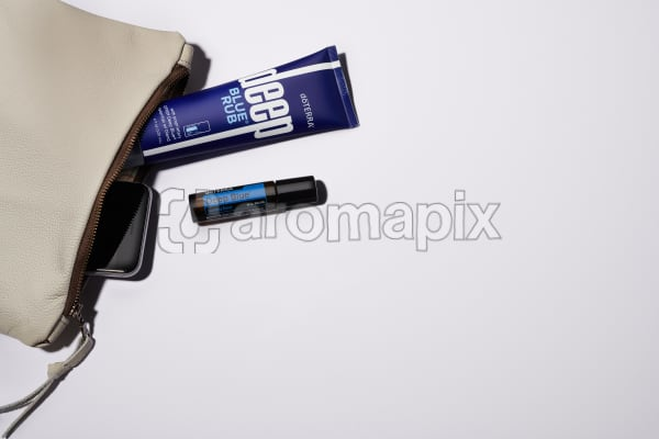 Woman's leather clutch with Deep Blue Rub,Deep Blue Touch and phone in bright midday sun with a white background.