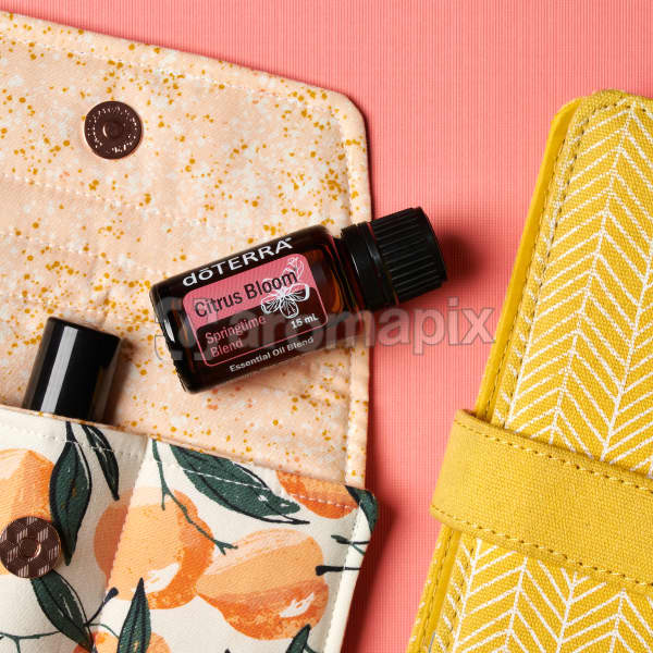 doTERRA Citrus Bloom on an essential oil bag with a yellow diary on a coral pink textured background.