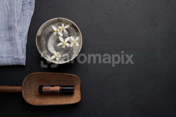doTERRA Neroli Touch in a wooden scoop with orange blosson flowers in a bowl of water on a black concrete backgrouns.