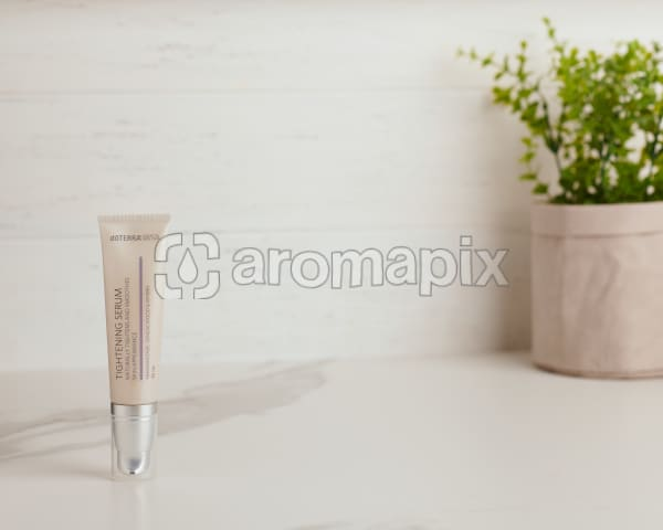 doTERRA Essential Skin Care Tightening Serum and a plant on a white marble bench.