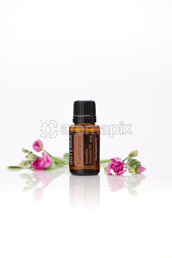 doTERRA Frankincense with flowers on a white background with reflection.