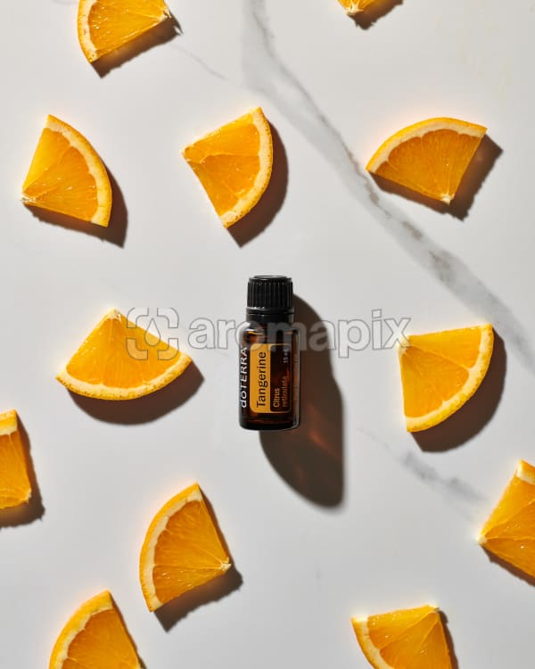 doTERRA Tangerine essential oil and citrus slices scattered on a white marble background.