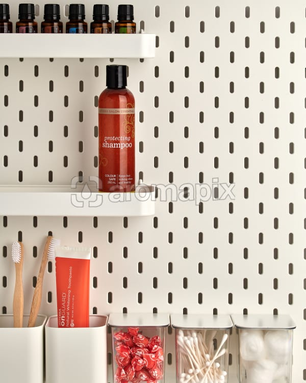 doTERRA Salon Essentials Protecting Shampoo on a bathroom shelf with bathroom accessories and additional doTERRA products.