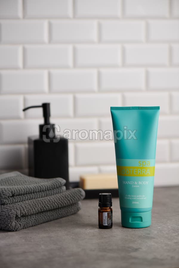 doTERRA Spa Hand and Body Lotion and Roman Chamomile essential oil with bathroom accessories on stone bench