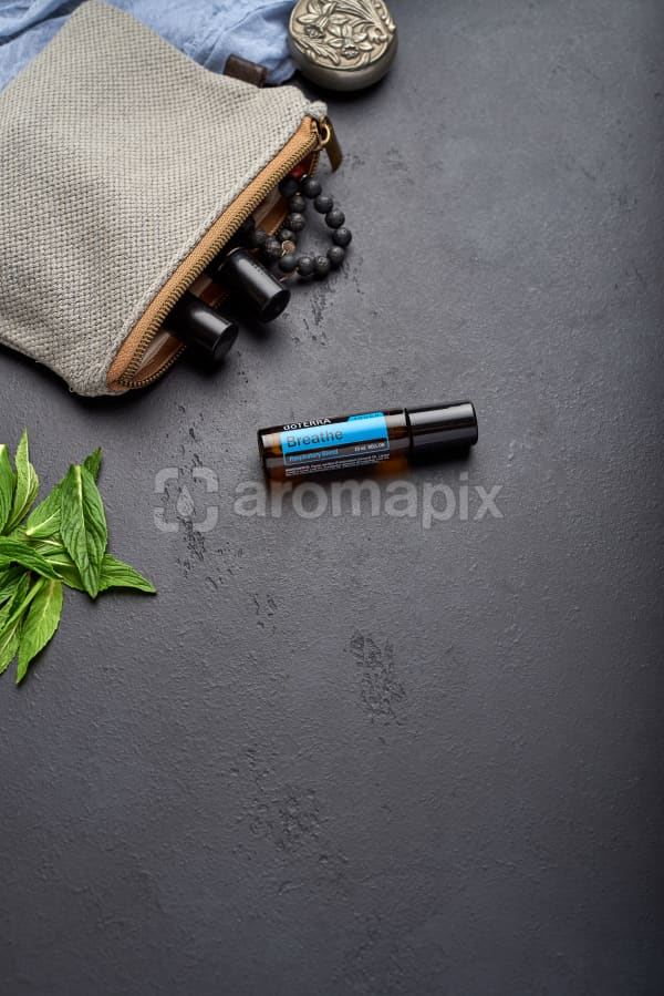 doTERRA Breathe Touch with clutch, accessories and mint leaves on a black concrete background.