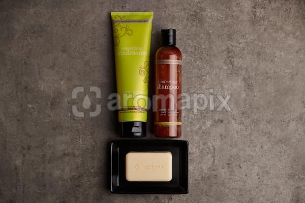 doTERRA Salon Essentials Shampoo and Conditioner  with a doTERRA Spa Moisturizing Bath Bar in a black soap dish on a gray stone bathroom bench.