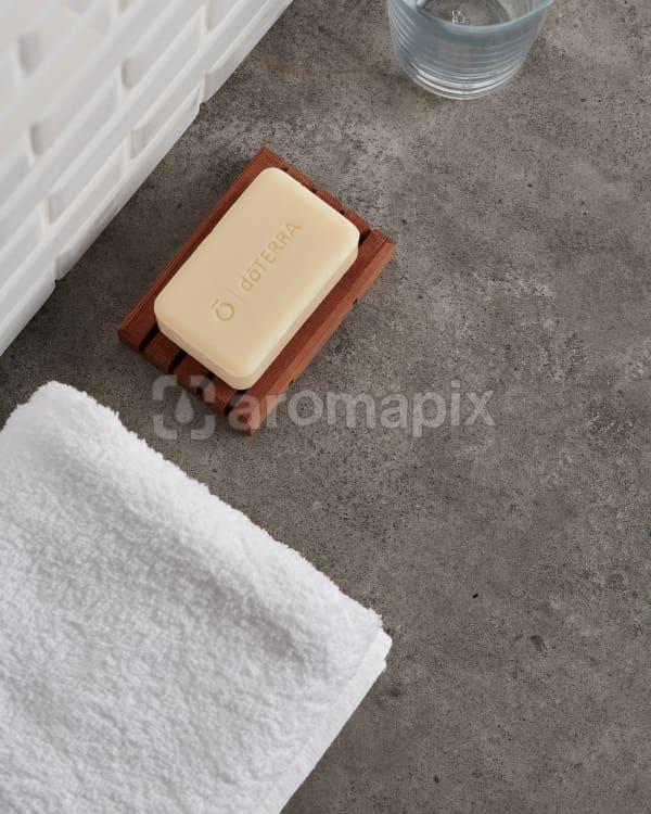 doTERRA Spa Moisturizing Bath Bar with a white fluffy towel on a stone bathroom bench top.