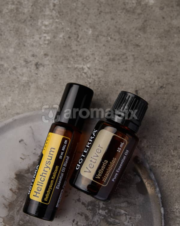 doTERRA Helichrysum Touch and Vetiver on a gray stone background.