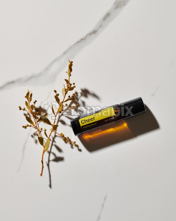 doTERRA Cheer Touch essential oil blend and a plant stem in direct sunlight on a white marble background.