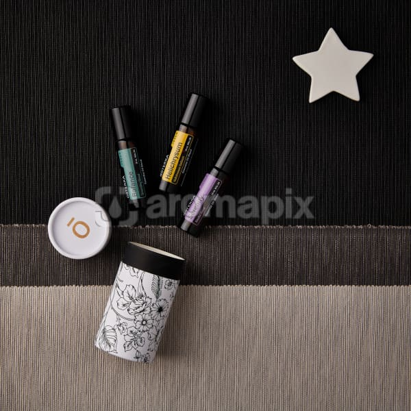doTERRA Balance Touch, Helichrysum Touch, and Serenity Touch with holiday decorations on a dark, medium and light gray textured background.