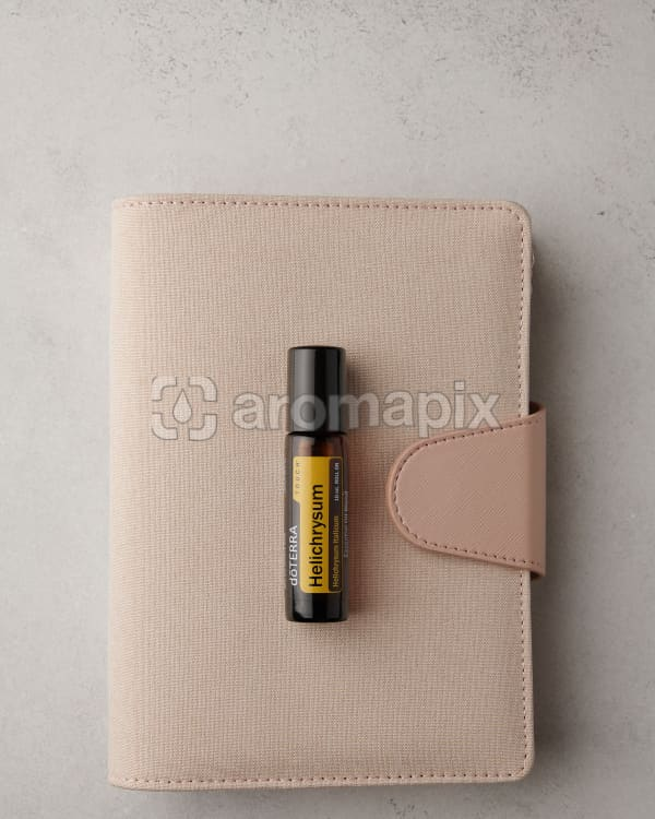 doTERRA Helichrysum Touch and a pink planner on a white stone benchtop.
