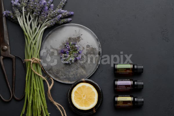 doTERRA Rosemary, Lavender and Lemon with lavender flowers, rosemary flowers, lemon slice and rustic utensils on a black concrete background.