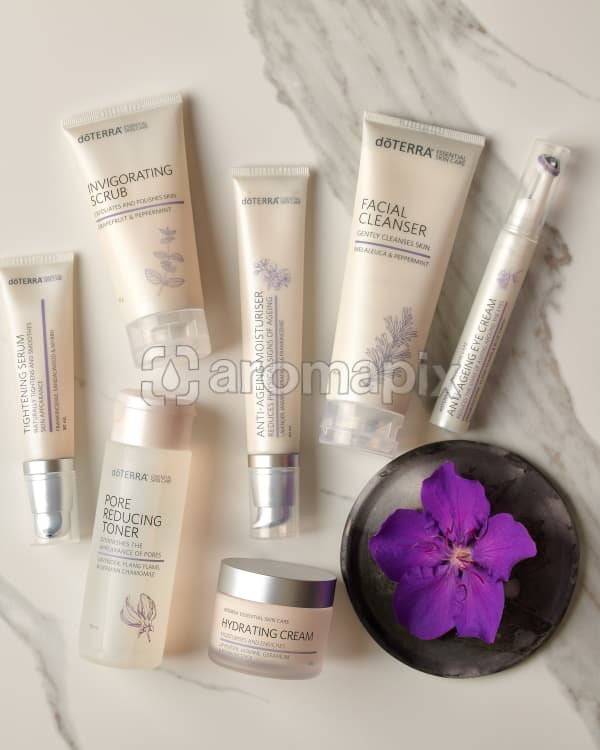 doTERRA Tightening Serum, Pore Reducing Toner, Invigorating Scrub, Anti-Ageing Moisturiser, Hydrating Cream, Facial Cleanser and Anti-Ageing Eye Cream with a purple flower in a gray ceramic plate on a white marble background.
