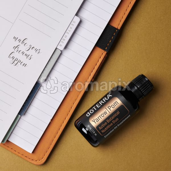doTERRA Yarrow Pom and an open journal with an inspirational quote on a golden background.