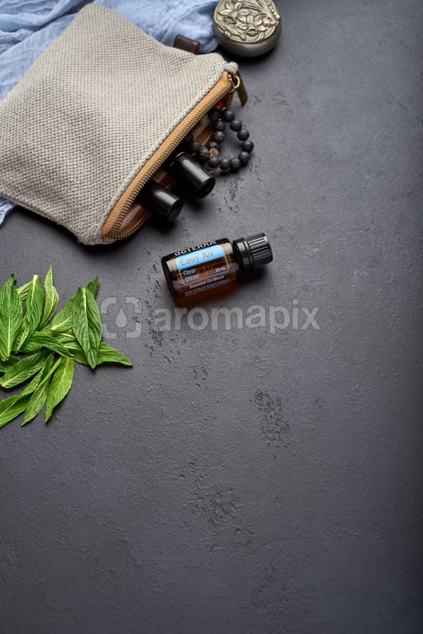 doTERRA Easy Air with clutch, accessories and mint leaves on a black concrete background.