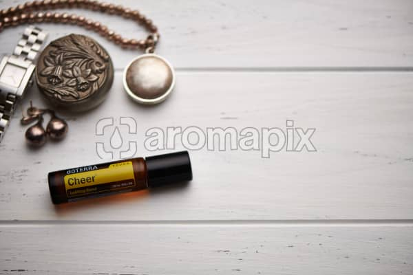 doTERRA Cheer Touch blend, jewellery and trinkets on white rustic wooden background.