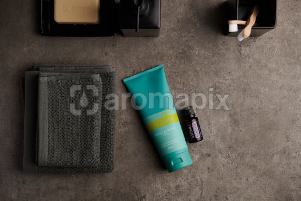 doTERRA Spa Hand and Body Lotion with Patchouli essential oil with bathroom accessories on a stone background.