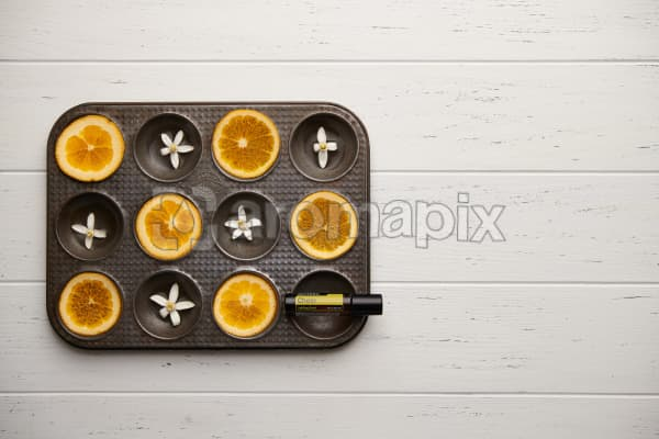 doTERRA Cheer Touch with seville orange slices and orange blossoms in a vintage baking tray on a white wooden background.