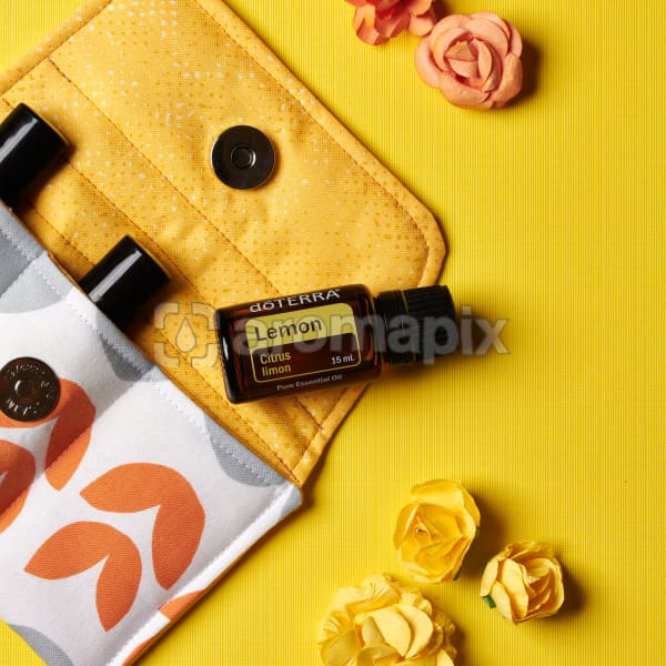 doTERRA Lemon on an essential oil bag with scattered flowers on a yellow textured background.