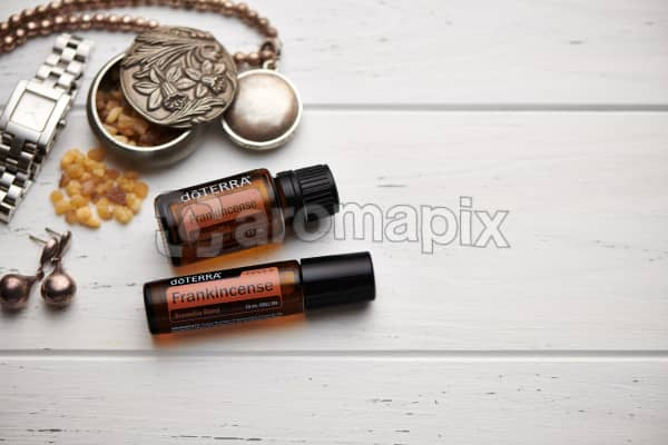 doTERRA Frankincense oil, Frankincense Touch and frankincense resin, jewellery and trinkets on white rustic wooden background.