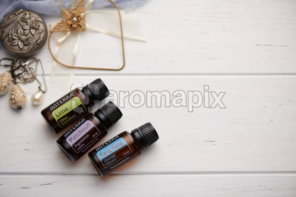 doTERRA Lime, Patchouli and Ylang Ylang oils with romantic jewellery on a white vintage wooden background.