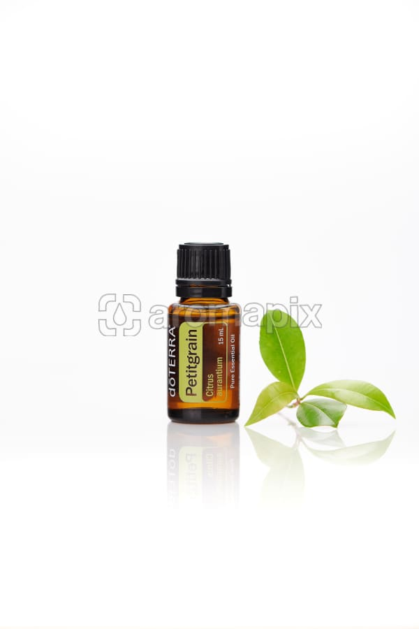 doTERRA Petitgrain with leaves on a white background with reflection.