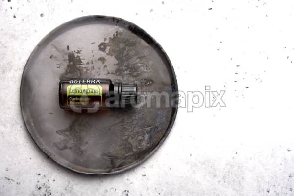 doTERRA Lemongrass on a rustic ceramic plate on a white concrete background.